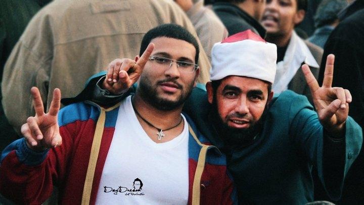 Cristiano copto e imam islamico alzano le dita in segno di vittoria