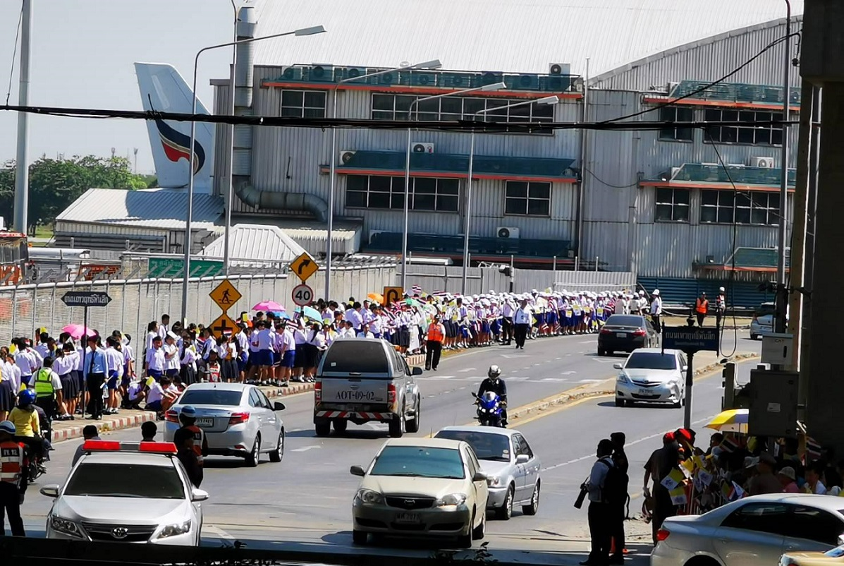Catholics await the arrival of the Pope outside the airport