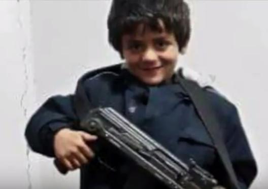 foto n.7 - Hadjem fotografato col mitra e davanti alla bandiera di Daesh